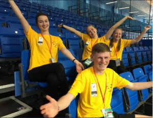 Four volunteers in yellow t-shirts sit in the empty bleacher seats overlooking the squash court in the Arena